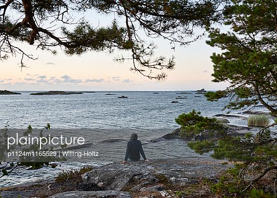 Frau sitzt auf Felsen an Schärenküste - p1124m1165529 von Willing-Holtz