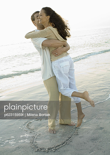 Couple standing on in heart shape on beach