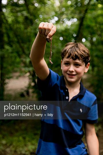 Junge mit Regenwurm im Wald - p1212m1152941 von harry + lidy