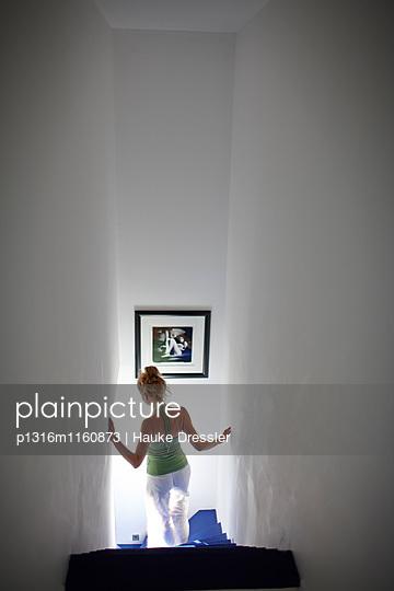 Frau geht Blaue Treppe in der Maison Des Terrasses hinunter, Hotel Les Andeols, Saint-Saturnin-les-Apt, Provence, Frankreich - p1316m1160873 von Hauke Dressler