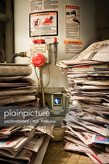 Piles of newspapers next to lit gas boiler