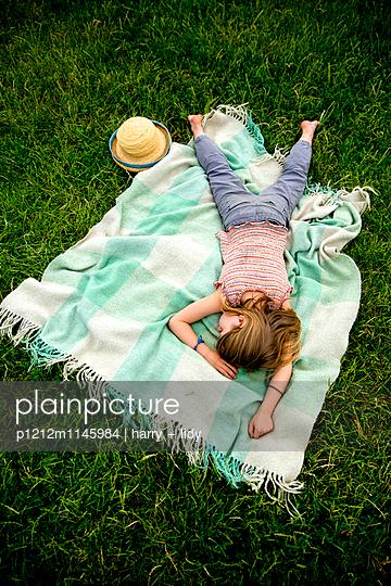 Mädchen schläft auf der Decke im Garten - p1212m1145984 von harry + lidy