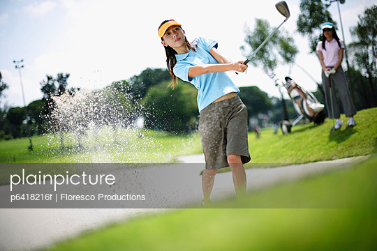 Woman playing golf with woman in background