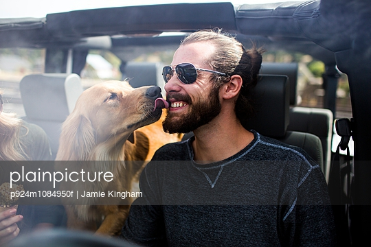 Dog licking young mans bearded face in jeep