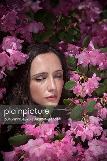 Wunderschöne Frau im Rhododendren-Strauch - p045m1154675 von Jasmin Sander