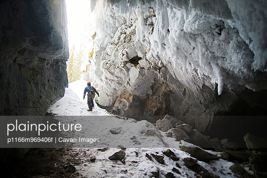 Man Exiting Dark and Icy Cave
