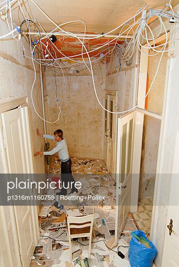 Frau spachtelt Tapeten von den Wänden einer Altbauwohung, Leipzig, Sachsen, Deutschland - p1316m1160759 von Roetting+Pollex