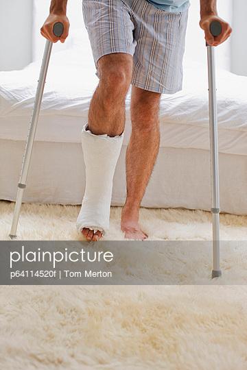 Man with broken leg walking on crutches