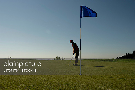 Man on golf course preparing to putt