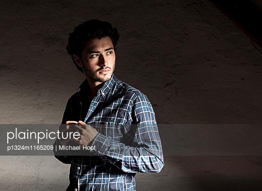 Junger Mann knöpft sein Hemd zu - p1324m1165209 von michaelhopf