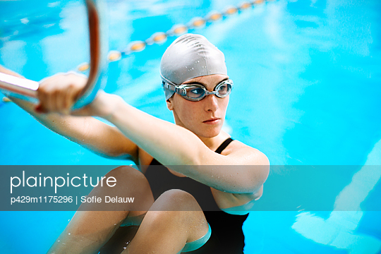 Woman in swimming pool holding starting block