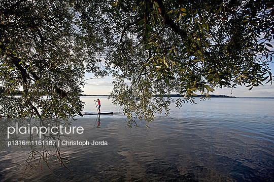 Frau beim Stand Up Paddling auf dem Chiemsee, Chiemgau, Bayern, Deutschland - p1316m1161187 von Christoph Jorda
