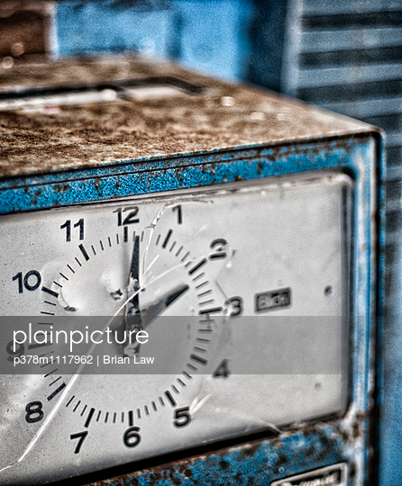Close-up of rusted and worn clocking-in clock