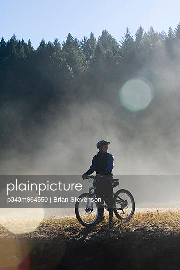 Man looks through fog and mist at start of a mountain bike race training run.