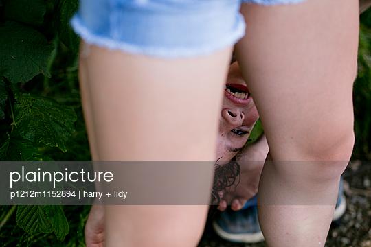Mädchenbeine - dahinter Junge Kopfüber - p1212m1152894 von harry + lidy