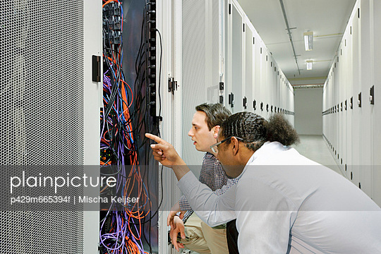 Businessmen examining wires in server