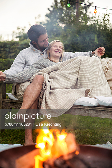 Junges Paar kuschelt auf der Gartenbank - p788m1165291 von Lisa Krechting