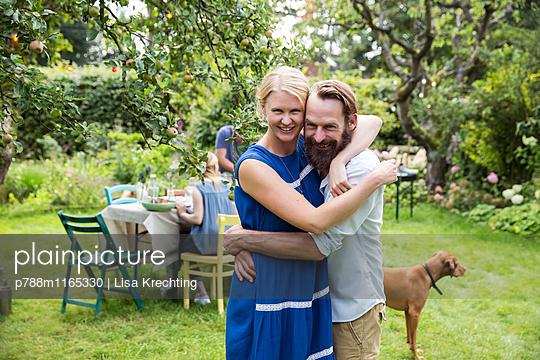 Paar umarmt sich im Garten - p788m1165330 von Lisa Krechting