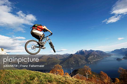 Italy, Lake Como, man performing jump on bicycle