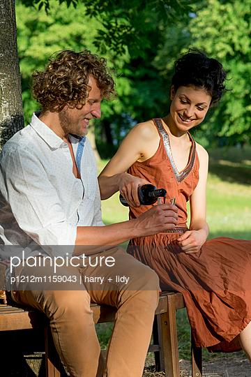 Paar beim Wein auf der runden Gartenbank - p1212m1159043 von harry + lidy