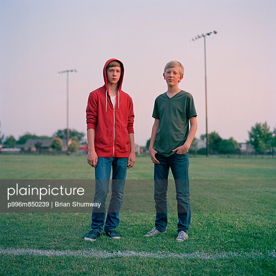 Portrait of two teenage brothers as they stand in the middle of an empty baseball field at a Discovery Park with stadium lights and a row of suburban homes behind. Pleasant Grove, UT