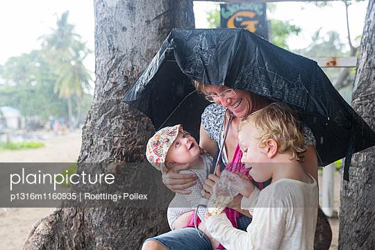 Familie im Regen, Regenschirm, Mutter mit zwei Kindern, Regen abwarten, lachen, Urlaub, Tropen, Insel, Baby, Mädchen 5 Monate, Junge 3 Jahre, Ferien, Elternzeit in Asien, Europäer, Deutsche, Westler, Familie, MR, Gili Air, Gili Inseln, Lombok, Indonesien - p1316m1160935 von Roetting+Pollex
