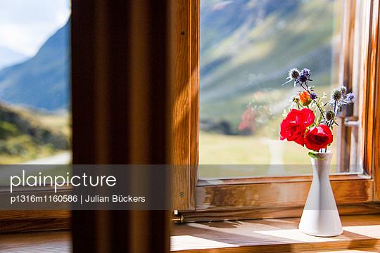 Morgenlicht bescheint eine Vase mit Bergblumen im Hüttenfenster, Fensterblick, Johannishütte, Prägraten, Virgental, Tirol, Österreich - p1316m1160586 von Julian Bückers