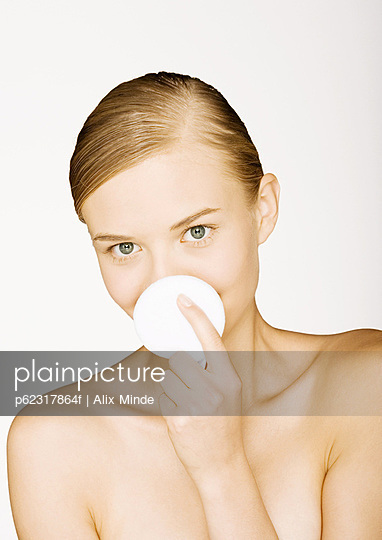 Woman holding up cotton pad in front of mouth