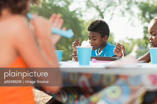 Children sitting at picnic table at birthday party