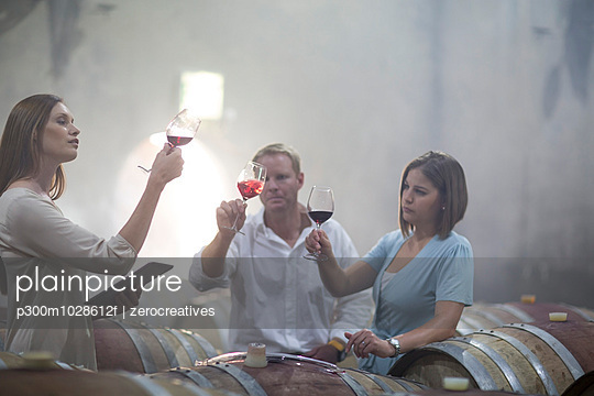 Three people tasting wine in cellar