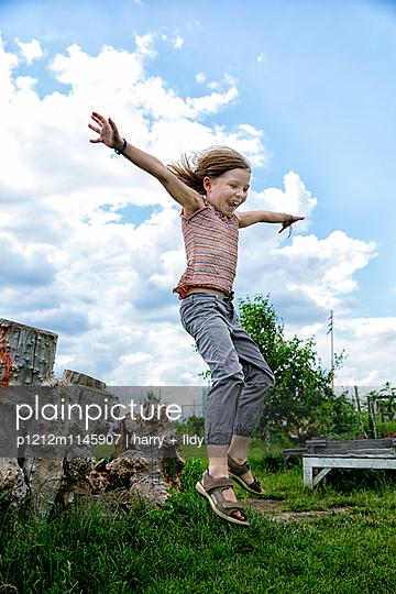 Mädchen springt vom Baumstumpf - p1212m1145907 von harry + lidy