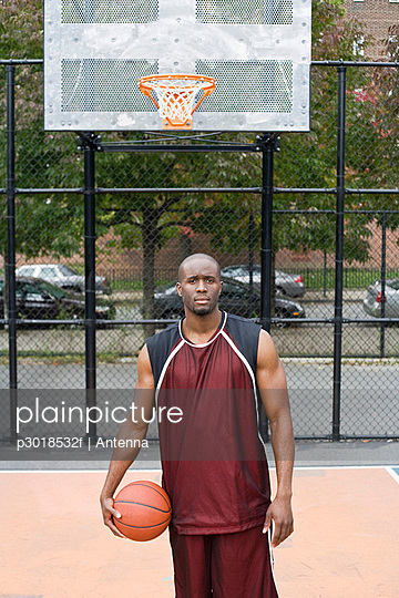 A basketball player holding a ball, portrait