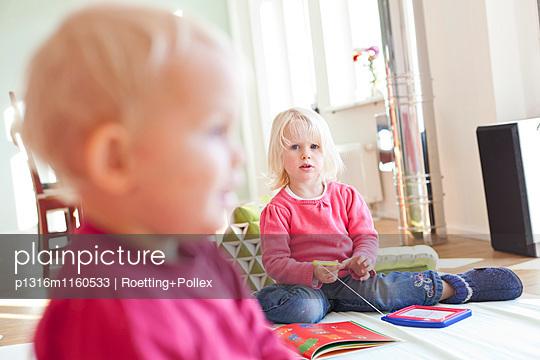 Zwei kleine Mädchen spielen im Wohnzimmer mit Spielzeug und Kinderbücher, 2 und 5 Jahre alt, MR, Leipzig, Sachsen, Deutschland - p1316m1160533 von Roetting+Pollex