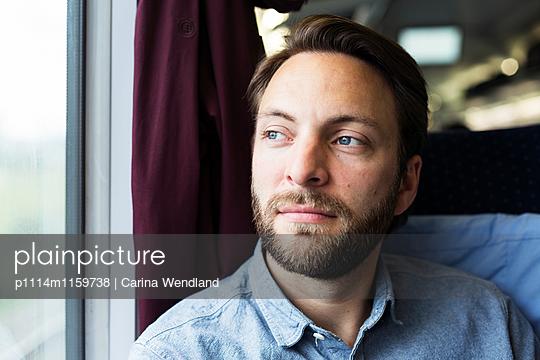 Mann schaut aus dem Zugfenster - p1114m1159738 von Carina Wendland