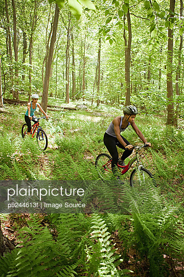 Two female cyclists in forest