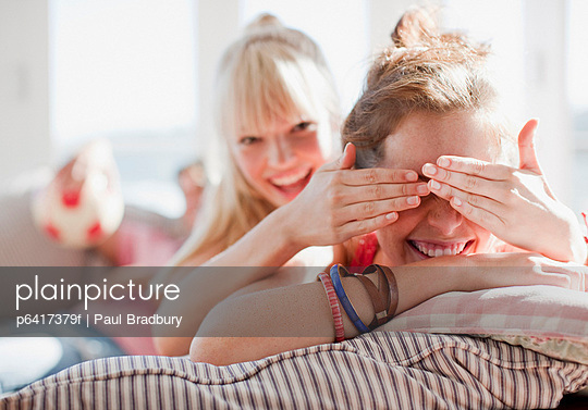 Woman covering friend's eyes