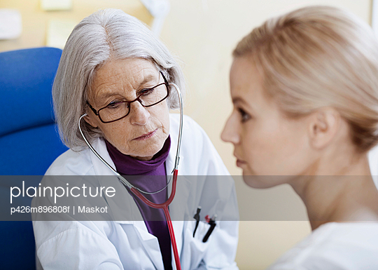 Senior female doctor examining patient in clinic