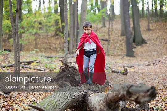 Boy (5-6) in costume walking on log in forest