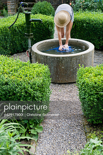 Woman filling watering can in pond