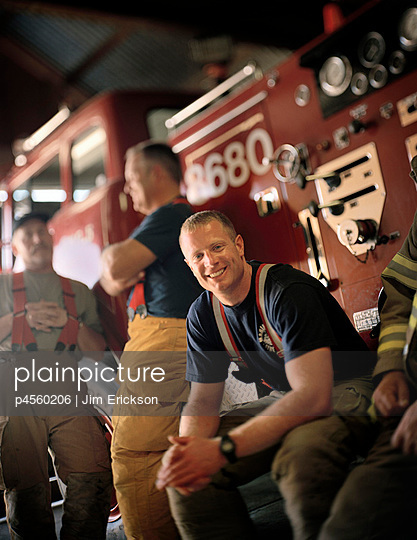 A fireman smilingly looks at the camera.