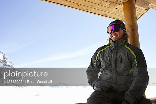 Man relaxing on ski lodge balcony