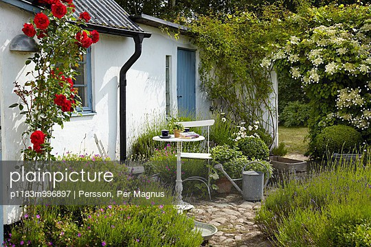 Small table and chairs in front of white-painted house