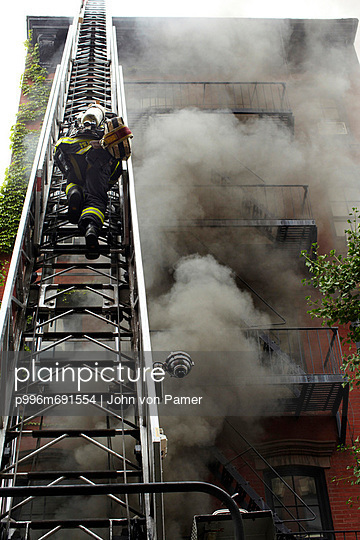 Firefighter Climbing Ladder In Front Of Burning Building.
