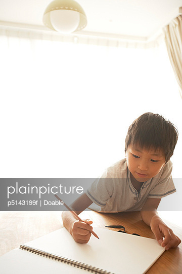 Boy drawing in sketch pad on floor