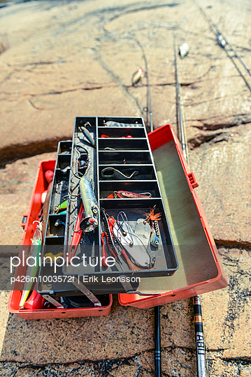 Open box with fishing gear on rock