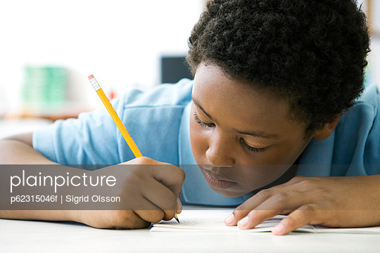 Male elementary school student concentrating on classwork