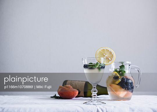 Water with fresh fruits and bottle of white wine