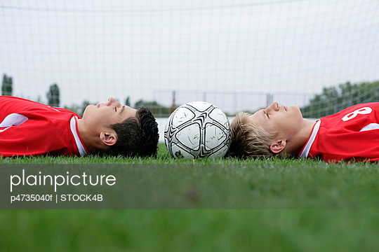 Two soccer players lying head to head, football between them