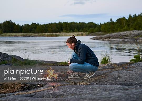 Frau macht Lagerfeuer - p1124m1165530 von Willing-Holtz