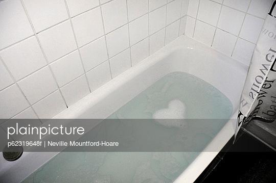 Soap suds forming heart shape in bathtub